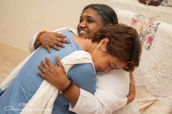 Amma embracing a woman