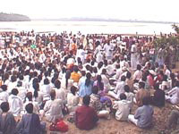 Amma with devotees by the river