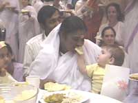 A baby sharing food with Amma