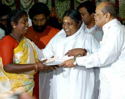 Amma handing out pensions to a widow
