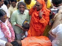 Swami of Narayana Guru Chaitanya Peetham offering padapuja to Amma