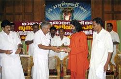 Swami Amritakripananda Puri hands over keys of tsunami houses to Mr. Chandy