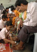 Children performing pada puja on their parents