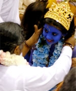 Amma with a child dressed up as Sri Krishna