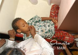 Amma playing with a sleeping child