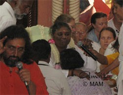 Amma giving darshan and talking on the mike