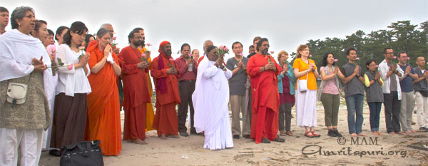 Amma offering prayers and flowers at the sea