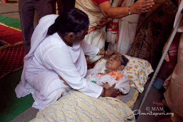 Amma consoling a bed-ridden